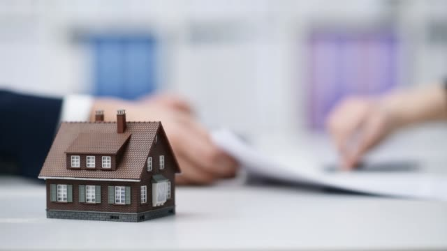 Real estate agent and customer signing a contract, the woman is buying a new home, model house in the foreground