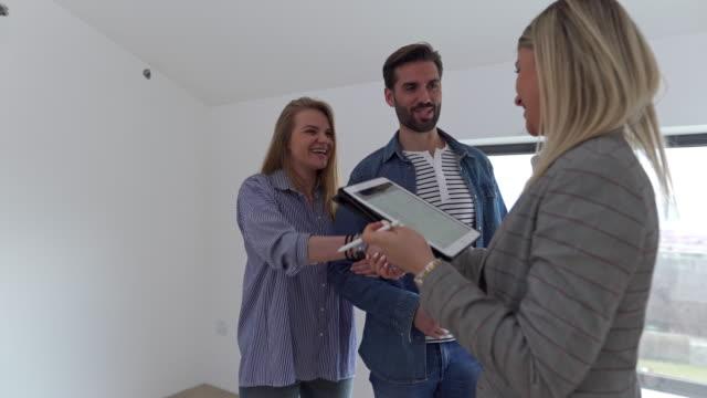 vídeos de stock, filmes e b-roll de agente imobiliário parabenizando um jovem casal por comprar uma casa nova. - condominio