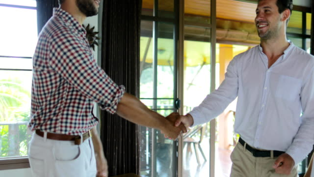 vídeos de stock e filmes b-roll de real estate agent giving keys of new home to happy couple, young man and woman buying modern apartment, businessman shaking hands - etnicidade ibérica