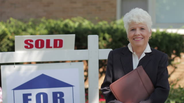 Real estate agent in front of a sold house video