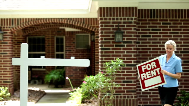 """Real estate agent places """"For Rent"""" sign. Home. A female real estate agent places a """"For Rent"""" sign in front of a home she is renting.  The rental property is a red brick home and the agent happily walks toward the post to place the sign in the yard. Summer. house rental stock videos & royalty-free footage"""