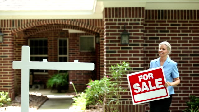 Real estate agent places 'For Sale' sign. Home. video