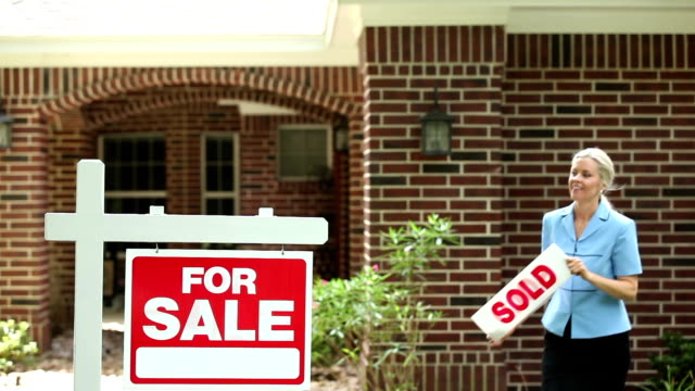 Real estate agent places sold sign on home for sale. video