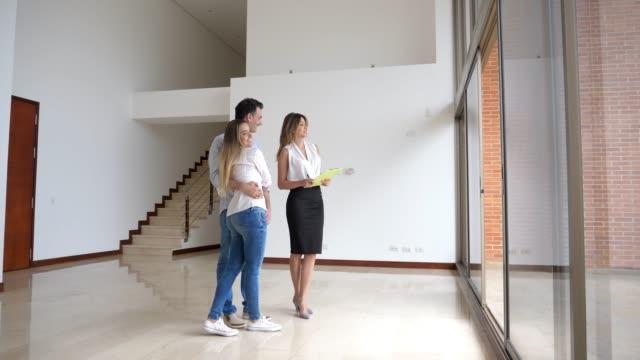 fastighetsmäklare som visar ett ungt par en modern lägenhet båda ser väldigt glad - fast egendom bildbanksvideor och videomaterial från bakom kulisserna