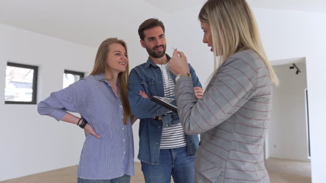 Real estate agent showing a young couple a new house
