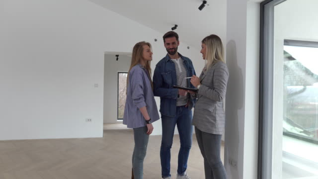 Real Estate Agent Shows Bright New Apartment to a Young Couple