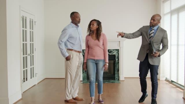 fastighetsmäklare visar att presumtiva bostadsköpare - fast egendom bildbanksvideor och videomaterial från bakom kulisserna