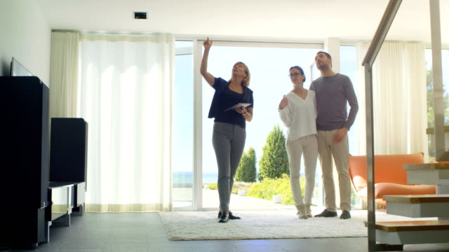 Real Estate Agent Shows Smart House Controlled with Tablet Computer to a Beautiful Young Couple. House Has Floor to Ceiling Windows and Seaside View.