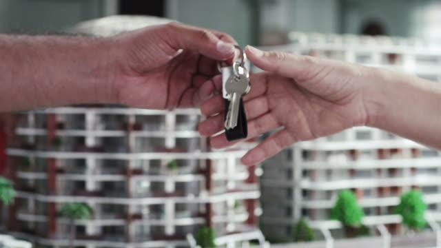 vídeos y material grabado en eventos de stock de mercado de bienes raíces. negocio apretón de manos y dar las claves - hipotecas y préstamos
