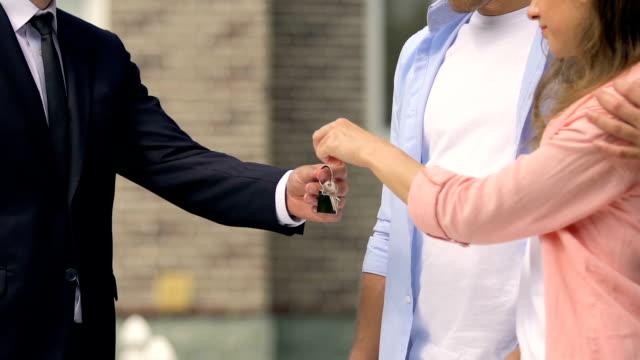 immobilienverkäufer geben schlüssel für junges paar und hände schütteln, familienhaus - hausschlüssel stock-videos und b-roll-filmmaterial