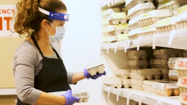 vídeos de stock, filmes e b-roll de vida real: funcionária de supermercado usando máscara facial protetora e escudo facial reabastecendo as prateleiras refrigeradas com embalagens de ovos orgânicos - ave doméstica