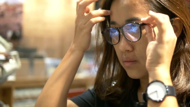 real people choosing glasses at store - оптический инструмент стоковые видео и кадры b-roll