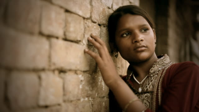 Real people from rural India: girl moving fingers on wall