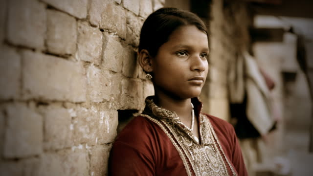Real people from rural India: girl standing against brick wall
