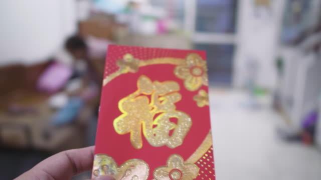 vidéos et rushes de vraies personnes obtiennent des paquets rouges de nouvelle année. - nouvel an chinois