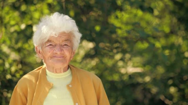 vídeos de stock, filmes e b-roll de pessoas reais mulher sênior, olhando para a câmera e sorrindo. - mulheres idosas
