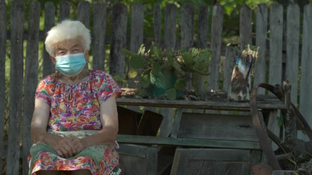 Real People Senior Woman Wearing Mask to Avoid Infectious Diseases. Looking at Camera and Smiling