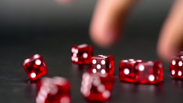 Real Slow motion throwing many red dices on black background