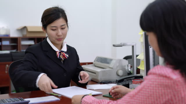 Real Time MS Business Talk Between bank Teller and Client The bank clerk is to handle the business for the customer,shanghai,china. bank counter stock videos & royalty-free footage