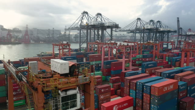 Real time crane shot container port 4k aerial view in real time with crane down shot of Hong Kong commercial container port in day time. cargo container stock videos & royalty-free footage