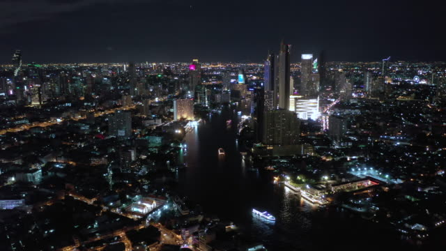 Real time dolly right of Chao Phraya River with Bangkok cityscape aerial view