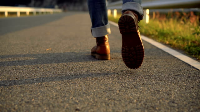 Real time of man in boots walking with orange warm light in the evening video