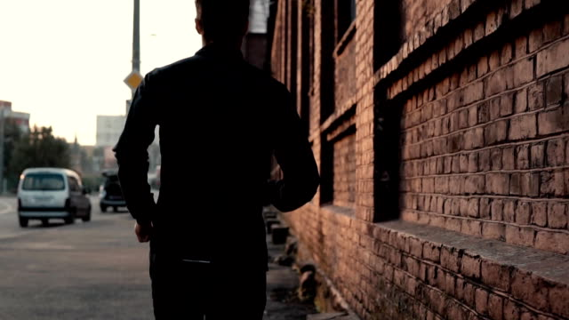 Real time sportsman running fast in an old street. Young free determined professional male fitness coach. Back view video