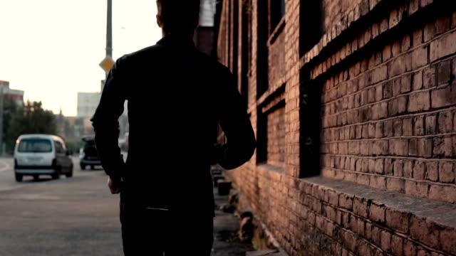 vidéos et rushes de temps réel sportif de courir vite dans une vieille rue. gratuit jeune déterminé préparateur physique masculin professionnel. vue arrière - course poursuite
