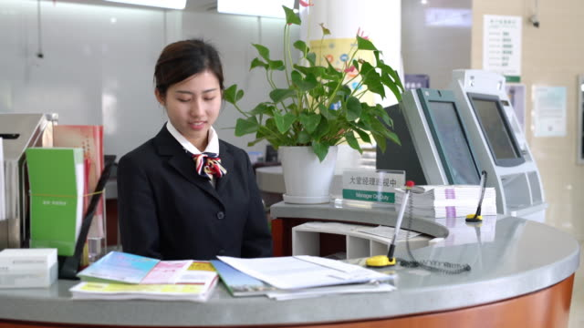 Real Time The bank clerk is entertaining clients at the front desk The bank clerk fill out a form for customer,shanghai,china. bank counter stock videos & royalty-free footage