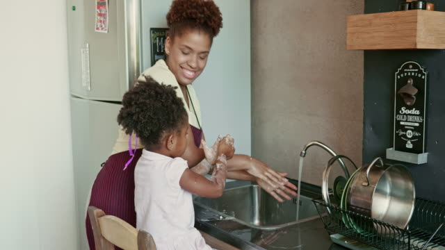 Real Time Video of Afro-Caribbean Mother and Daughter Washing Hands at Kitchen