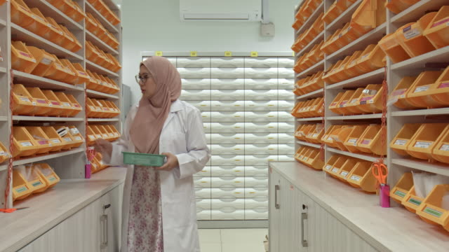 real time video of asian muslim pharmacist working at pharmacy - abbigliamento religioso video stock e b–roll