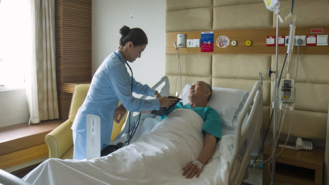 real time video of asian nurse checking senior man's blood pressure at hospital - nurse filmów i materiałów b-roll