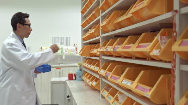 vidéos et rushes de vidéo en temps réel du pharmacien asiatique travaillant sur une ordonnance à la pharmacie - pharmacie