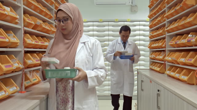 real time video of asian pharmacists choosing medication at pharmacy - abbigliamento religioso video stock e b–roll