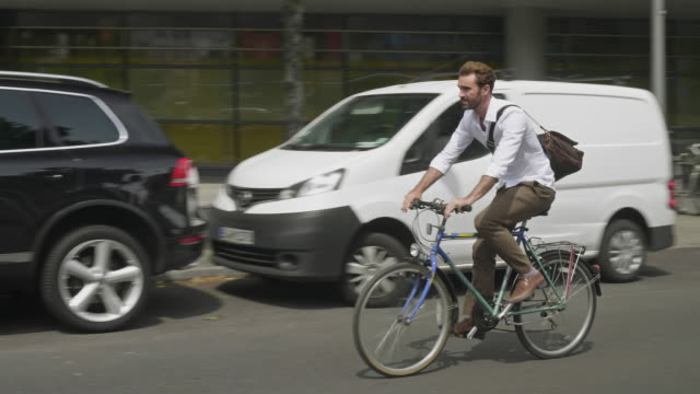 Real time video of businessman commuting by bicycle in the streets of Berlin Real time video of businessman commuting by bicycle in the streets of Berlin. mid adult men stock videos & royalty-free footage