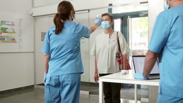 wideo w czasie rzeczywistym różnych ludzi mających kontrolę pandemii przy wejściu do szpitala - sprawdzać filmów i materiałów b-roll