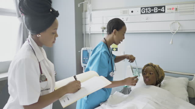 Real time video of female doctor with nurse attending patient in ward