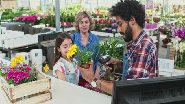 real time video of gardener using barcode scanner by family at shop - semenzaio video stock e b–roll