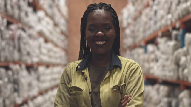 Real time video of happy female worker in aisle at warehouse Real time video of happy female worker in aisle at warehouse. place of work stock videos & royalty-free footage