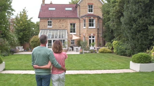 stockvideo's en b-roll-footage met real-time video van ouder paar omhelzen elkaar terwijl kijken naar hun nieuwe huis - garden house