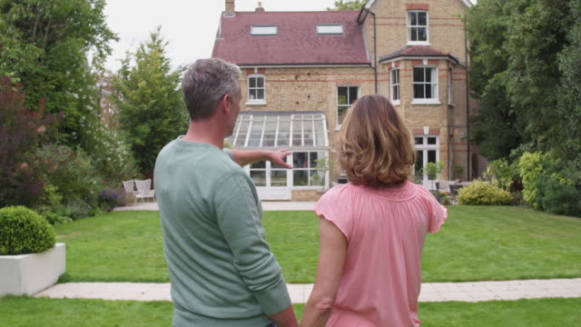 Real time video of mature couple standing in front of house talking about buying it Real time video of mature couple standing in front of house talking about buying it. renovation stock videos & royalty-free footage