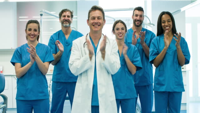 real time video of medical team clapping for the camera - battere le mani esprimere a gesti video stock e b–roll