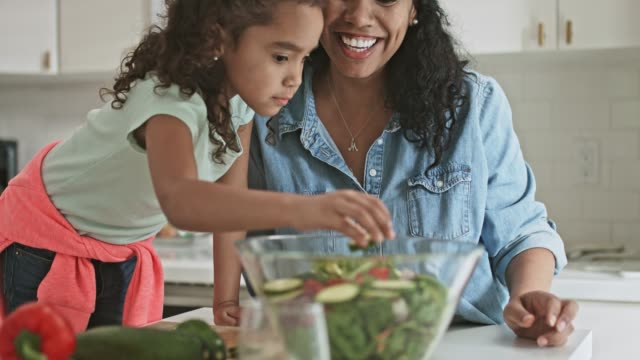 Real time video of mother and daughter preparing salad at home