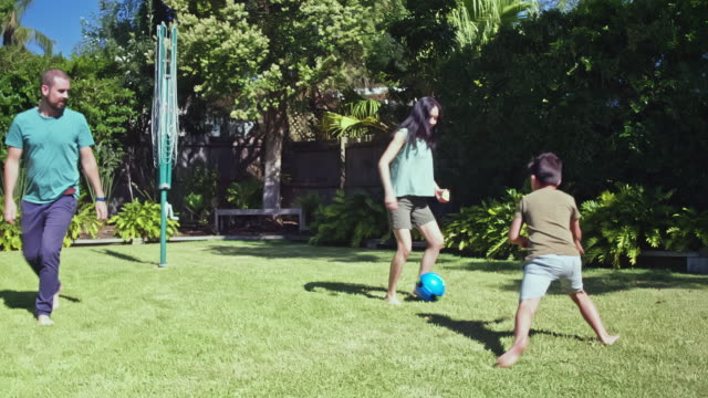 real time video of multi-ethnic australian family playing  at the backyard garden - формальный сад стоковые видео и кадры b-roll