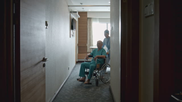 real time video of nurse taking patient into a health test from hospital room with wheelchair - infermiera personale medico video stock e b–roll