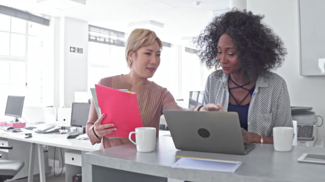 Real time video of two businesswomen talking about the new project in the office video