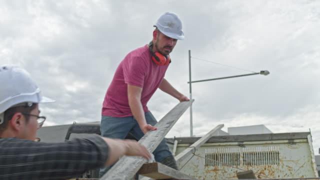 Vídeo en tiempo real de dos trabajadores de la construcción cargando la furgoneta con marcos de madera - vídeo
