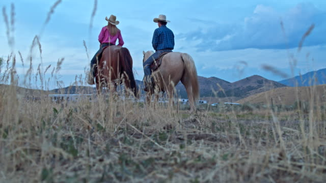 Real time video of two friends horseback riding at dusk in Utah Real time video of two friends horseback riding at dusk in Utah. cowgirl stock videos & royalty-free footage