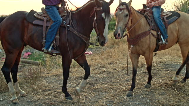 Real time video of two teenagers riding horses at sunset video
