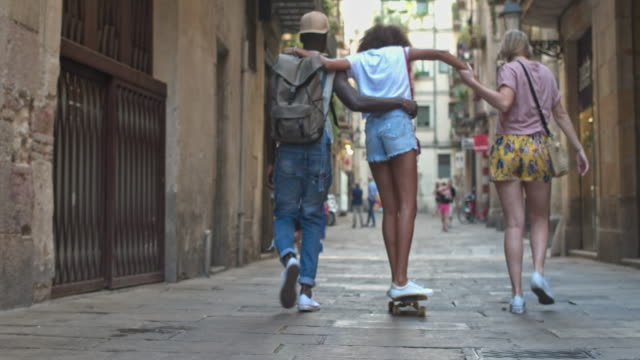 real time video of youngsters with skateboards walking on urban street - teenagers stock videos and b-roll footage